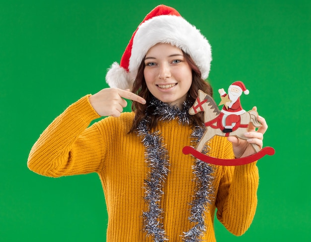 Pleased young slavic girl with santa hat and with garland around neck holding and pointing at santa on rocking horse decoration isolated on green background with copy space