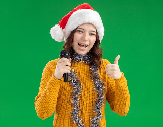 Pleased young slavic girl with santa hat and with garland around neck holds mic and thumbs up