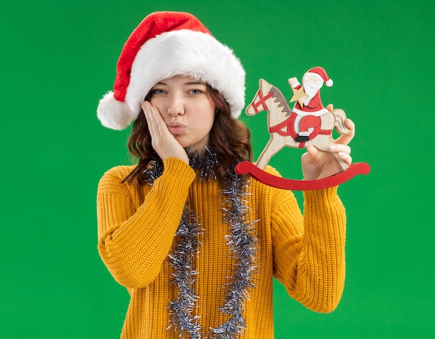 Pleased young slavic girl with santa hat and with garland around neck puts hand on face and holds santa on rocking horse decoration