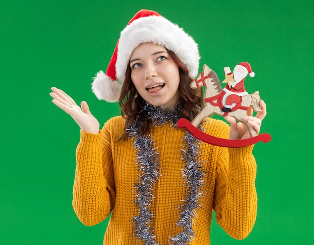Pleased young slavic girl with santa hat and with garland around neck stucks out tongue and holds santa on rocking horse decoration
