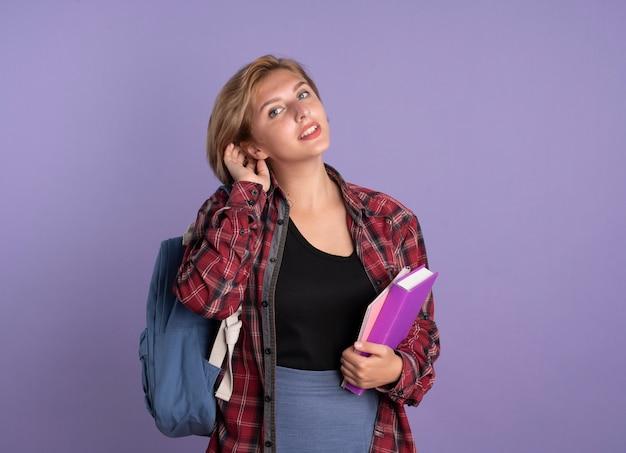 喜んでバックパックを着た若いスラブ学生の女の子が本を持ち、ノートが髪を持ち上げる