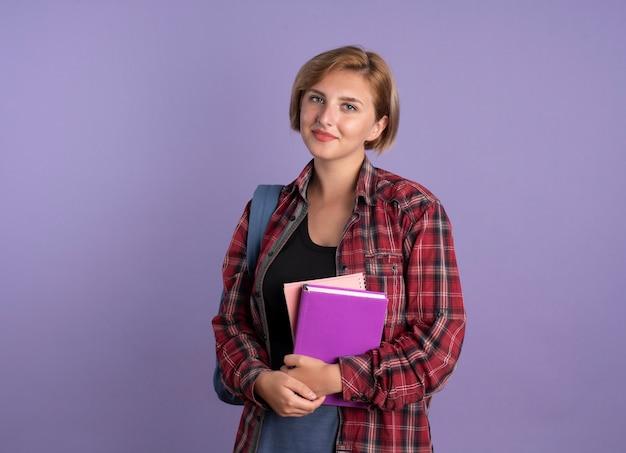 배낭을 입고 기쁘게 젊은 슬라브 학생 소녀 책과 노트북을 보유