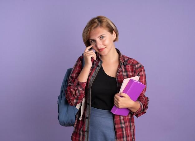 Довольная молодая славянская студентка в рюкзаке кладет палец на веко, держит книгу и тетрадь