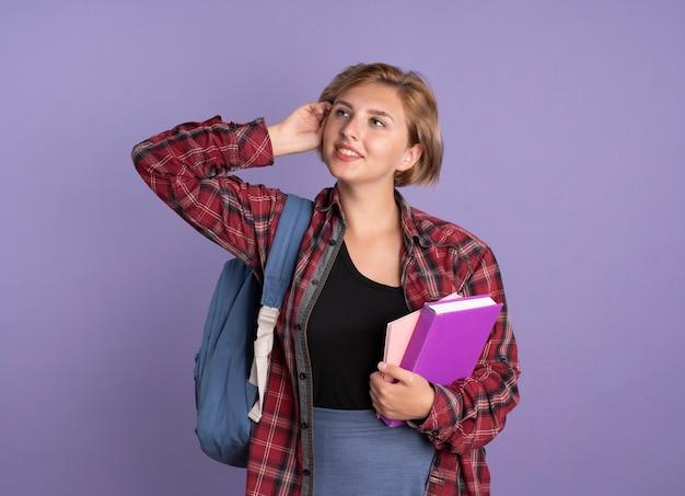Felice giovane studentessa slava che indossa uno zaino mette la mano sulla testa tiene un libro e un taccuino guardando a lato