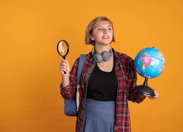 バックパックを着たヘッドフォンを付けた満足している若いスラブ学生の女の子が地球儀と虫眼鏡を持っている