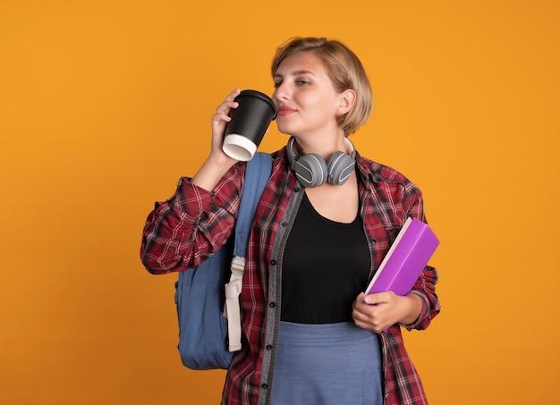 배낭을 착용하는 헤드폰으로 기쁘게 젊은 슬라브 학생 소녀는 종이 컵 책과 노트북을 보유하고 있습니다.