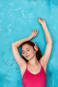 헤드폰으로 음악을 듣고 파란색 벽 위에 포즈를 취하는 젊은 스포츠 빨간 머리 여자를 기쁘게 생각합니다.