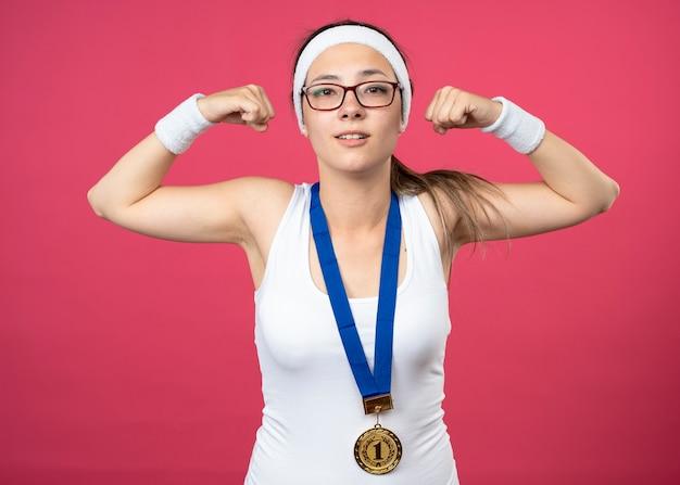 ヘッドバンドとリストバンドを身に着けている首の周りに金メダルを持つ光学メガネのスポーティな若い女の子を喜ばせ、上腕二頭筋を緊張させる