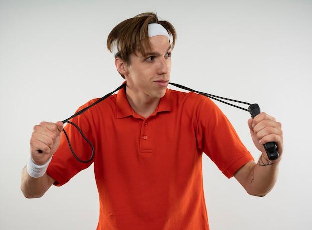 Довольный молодой спортивный парень смотрит в сторону, носит повязку на голову с браслетом, держащим скакалку на шее