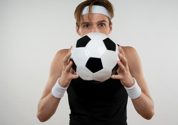 Довольный молодой спортивный парень в повязке на голову и браслет закрыл лицо мячом, изолированным на белом