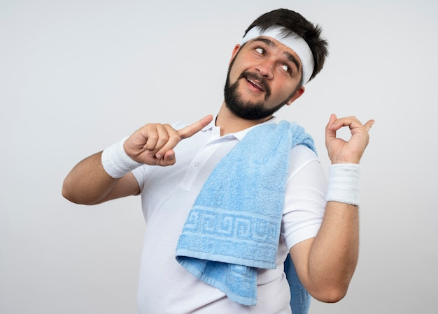 흰 벽에 고립 된 측면에서 어깨 포인트에 수건으로 머리띠와 팔찌를 입고 측면을보고 기쁘게 젊은 스포티 한 남자