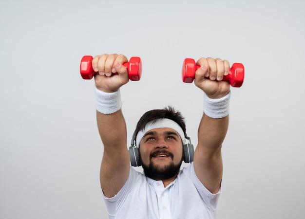 白で隔離のダンベルで運動しているヘッドバンドとリストバンドとヘッドフォンを身に着けて見上げる幸せな若いスポーティな男