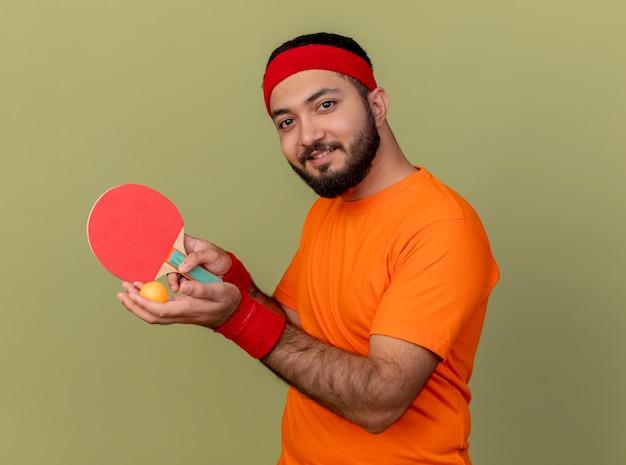 卓球のラケットを保持しているヘッドバンドとリストバンドを身に着けている若いスポーティーな男を喜ばせる