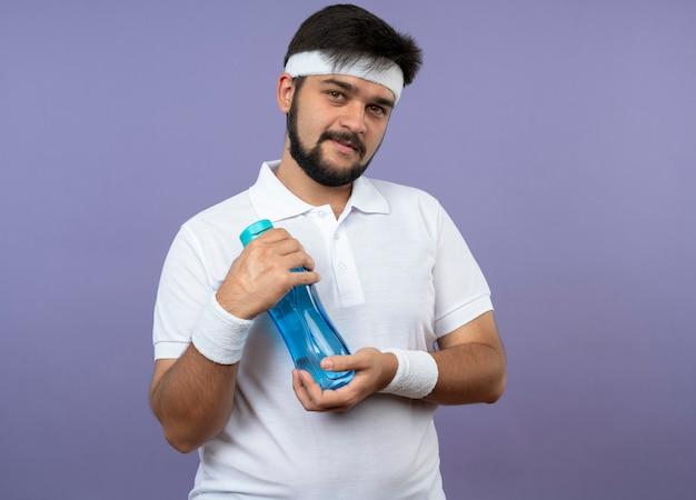 Довольный молодой спортивный мужчина с головной повязкой и браслетом держит бутылку с водой