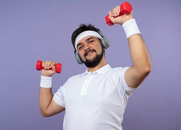 녹색 벽에 고립 된 아령으로 운동하는 헤드폰으로 머리띠와 팔찌를 입고 기쁘게 젊은 스포티 한 남자