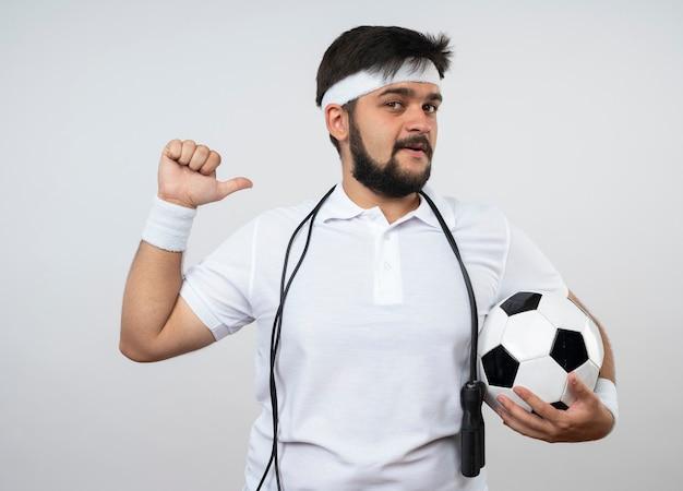 Довольный молодой спортивный мужчина в головной повязке и браслете со скакалкой на плече, держащий в руках шариковые очки, изолированные на белой стене