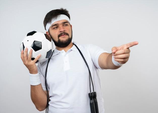 Довольный молодой спортивный мужчина с повязкой на голову и браслетом со скакалкой на плече, держащим шарики сбоку, изолированными на белой стене