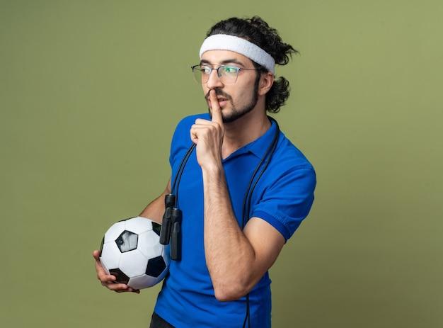 Довольный молодой спортивный мужчина с повязкой на голову с браслетом и скакалкой на плече держит мяч, показывая жест тишины