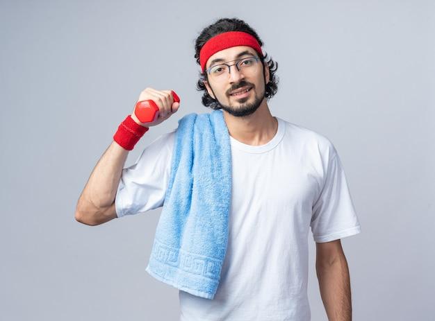 Довольный молодой спортивный мужчина с повязкой на голову с браслетом и полотенцем на плече, тренирующимся с гантелями