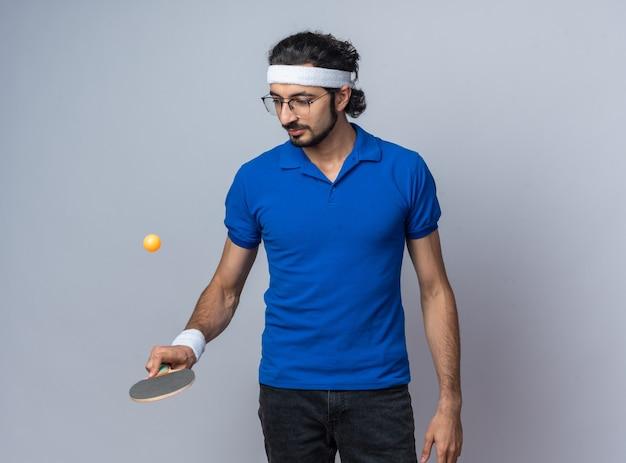 ラケットにピンポンボールを保持しているリストバンドとヘッドバンドを身に着けている若いスポーティな男を喜ばせる