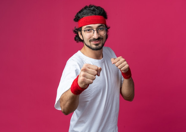 싸우는 포즈에 서 있는 팔찌와 머리띠를 착용하는 기쁘게 젊은 스포티 한 남자