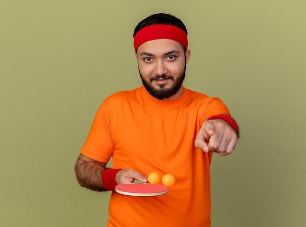 Lieto giovane sportivo da uomo che indossa la fascia e il braccialetto che tiene la racchetta da ping pong con palline e ti mostra il gesto isolato su sfondo verde oliva