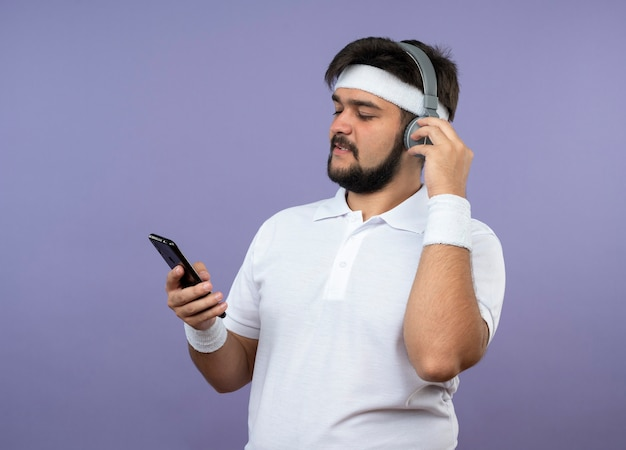 Pleased young sporty man wearing headband and wristband with headphones holding and looking at phone