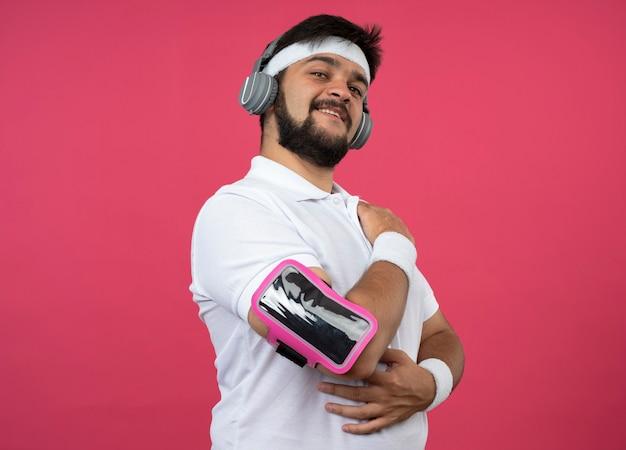 Soddisfatto giovane sportivo che indossa la fascia e il braccialetto con le cuffie e la fascia da braccio del telefono isolata sulla parete rosa