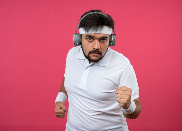 Pleased young sporty man wearing headband and wristband with headphones and phone arm band showing running gesture isolated on pink wall