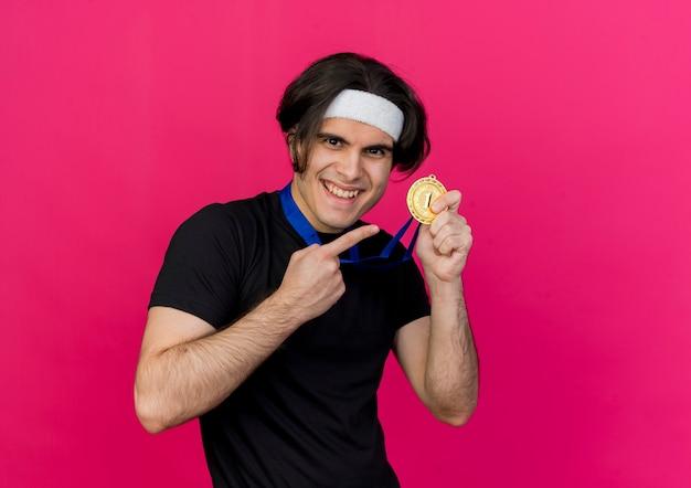 スポーツウェアとヘッドバンドを身に着けている若いスポーティな男がメダルを幸せな笑顔で人差し指で指して首の周りに金メダルを喜んで