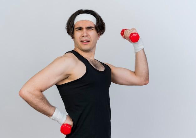 운동복과 머리띠를 착용하고 흰색 벽 위에 서있는 앞에서 포즈를 취하는 아령으로 운동을하는 기쁘게 젊은 스포티 한 남자