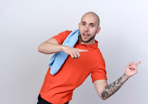 白い壁に隔離された側の肩のポイントにタオルで若いスポーティな男を喜ばせる