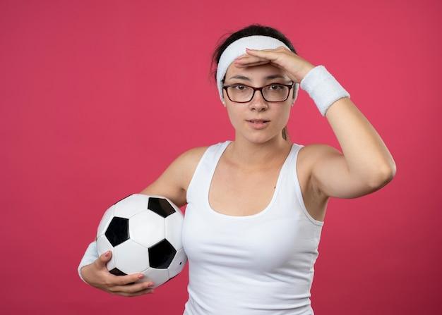 Piacevole giovane donna sportiva con occhiali ottici che indossa fascia e braccialetti mantiene il palmo sulla fronte e tiene la palla isolata sul muro rosa