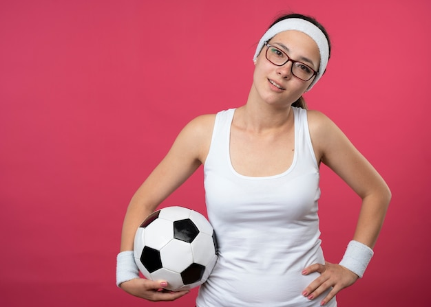 Pleased young sporty woman in optical glasses wearing headband and wristbands puts hand on waist and holds ball isolated on pink wall