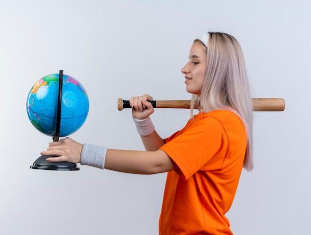 Lieta giovane donna sportiva con bretelle che indossano fascia e braccialetti si trova lateralmente tenendo la mazza da baseball e il globo isolato sul muro bianco