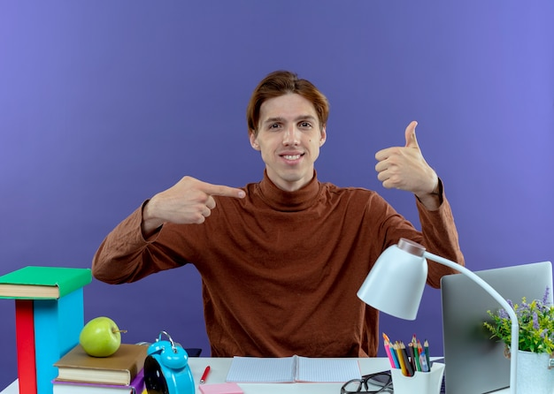 Pleased young studend boy sitting at desk with school tools showing different gestures on purple