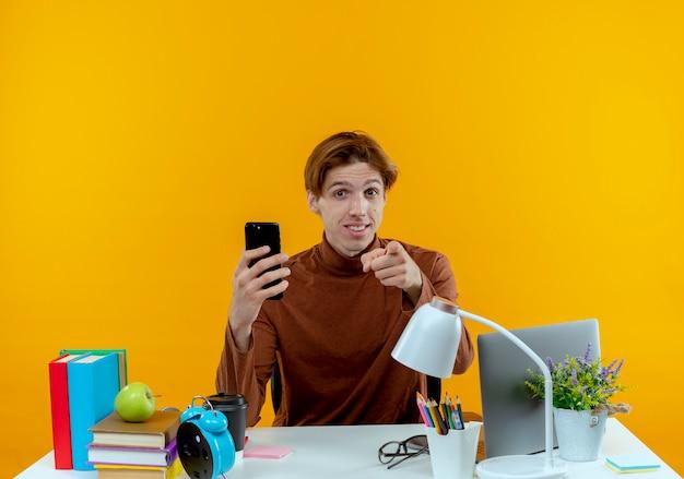 학교 도구 전화를 들고 노란색 벽에 고립 된 제스처를 보여주는 책상에 앉아 기쁘게 젊은 학생 소년