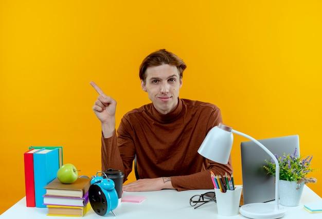 노란색 측면에서 학교 도구 포인트와 책상에 앉아 기쁘게 젊은 학생 소년