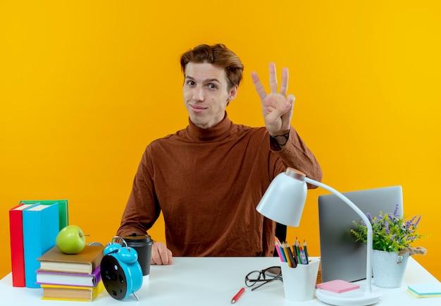 노란색 벽에 고립 된 세를 보여주는 학교 도구로 책상에 앉아 기쁘게 젊은 학생 소년