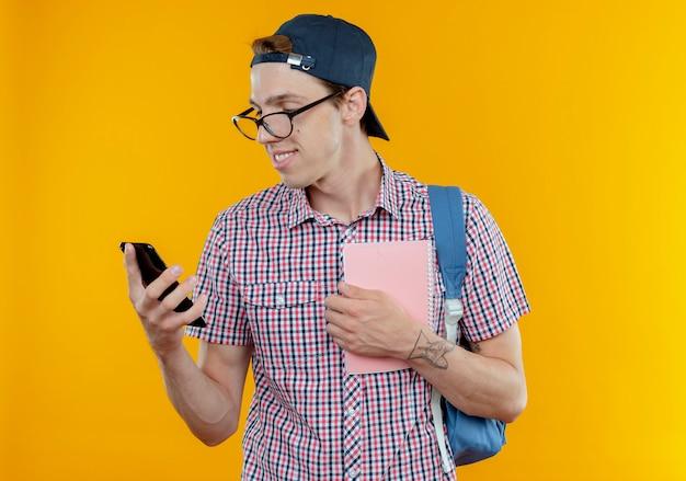 バックバッグとメガネとノートを保持し、白で隔離の彼の手で携帯電話を見てキャップを身に着けている若い学生の少年を喜ばせる