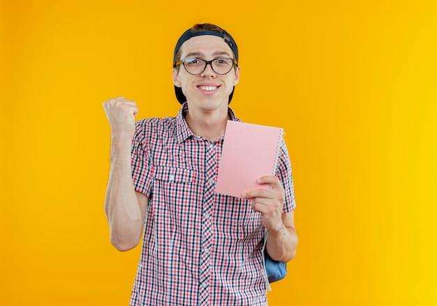 Довольный молодой студент мальчик в задней сумке и очках и кепке держит блокнот и показывает жест