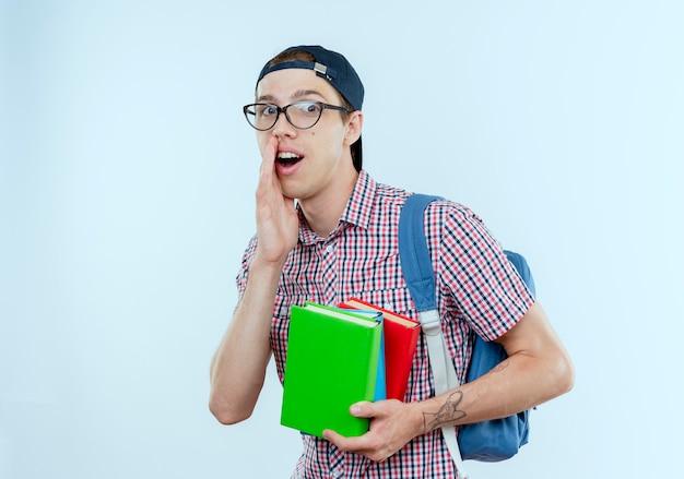 Soddisfatto giovane studente ragazzo che indossa borsa posteriore e occhiali e berretto in possesso di libri e sussurri su bianco