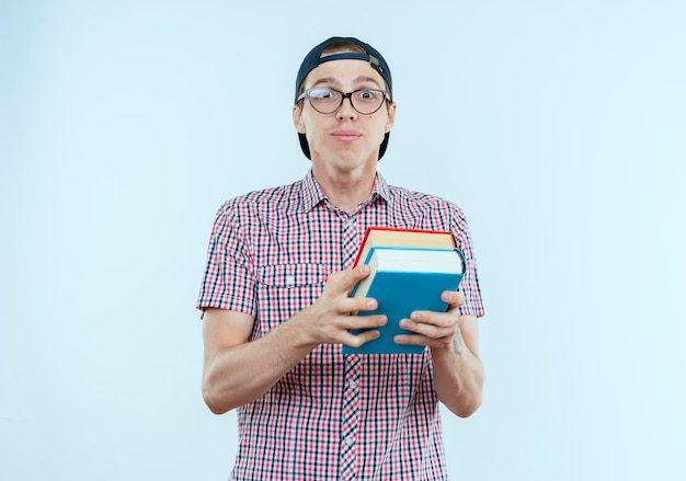 Pleased young student boy wearing back bag and glasses and cap holding books on white