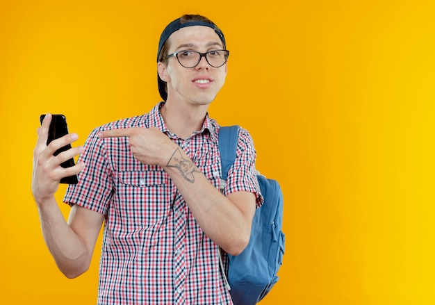 Pleased young student boy wearing back bag and glasses and cap holding and points at phone on white