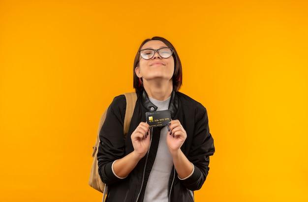 オレンジ色の壁に隔離された目を閉じてクレジットカードを保持している眼鏡とバックバッグを身に着けている若い学生の女の子を喜ばせる