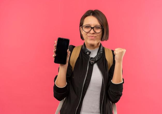 ピンクの壁に隔離された目を閉じて拳を握り締める携帯電話を保持している眼鏡とバックバッグを身に着けている若い学生の女の子を喜ばせる