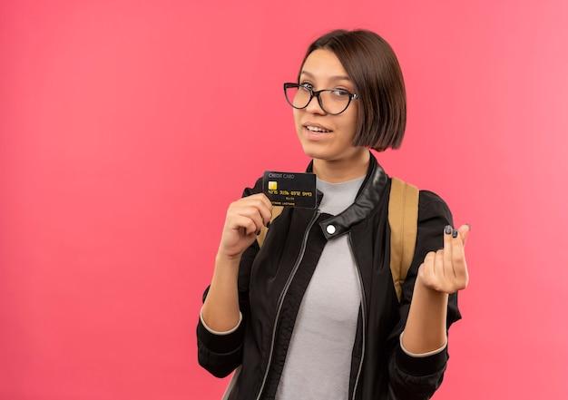 Lieta giovane studentessa con gli occhiali e borsa posteriore in possesso di carta di credito gesticolando denaro isolato sulla parete rosa