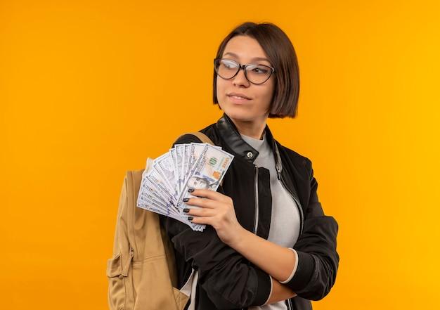 Felice giovane studente ragazza con gli occhiali e borsa posteriore in piedi con la postura chiusa tenendo i soldi guardando il lato isolato sulla parete arancione