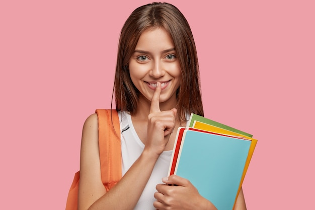 Довольный молодой студент позирует у розовой стены