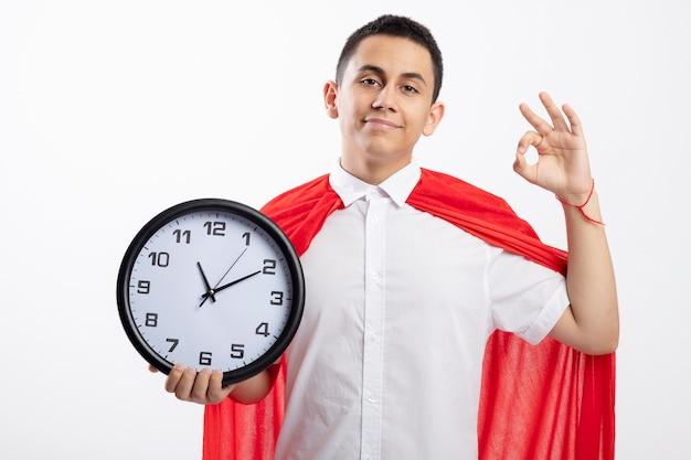 Довольный молодой супергерой мальчик в красной накидке, держащий часы, смотрящий в камеру, делает знак ок, изолированные на белом фоне